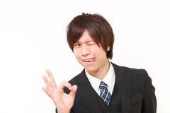 Junger japanischer Geschäftsmann, der perfektes Zeichen zeigt Stockbild