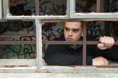 Junger Jugendlicher, der hinter einer zerbrochenen Fensterscheibe denkt lizenzfreie stockfotografie