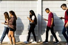 Junger Jugendlicher, der ihr Telefon untersucht stockbilder