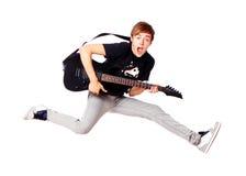 Junger Jugendlicher, der mit Gitarre springt Stockfotos