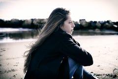 Junger Jugendlicher, der niedergedrücktem Sitzen vor dem Strand glaubt Lizenzfreies Stockfoto