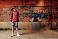 Junger Jugendlicher gegen Graffiti-Wand Stockbilder
