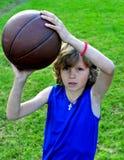 Junger Jugendlicher mit einem Basketball draußen Lizenzfreie Stockfotografie