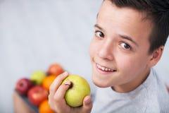 Junger Jugendlichjunge, der einen Apfel - oben schauend hält stockbilder