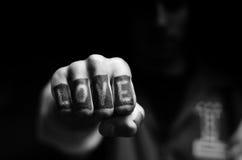 Junger Jugendmann, der den Liebestext tätowiert auf seinen Fingern zeigt Stockfotos