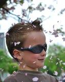 Junger Junge abgedeckt durch Blüte stockbild