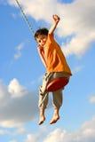Junger Junge auf Kettenschwingen stockfotos