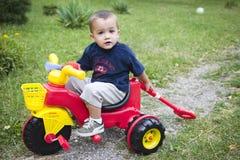 Junger Junge auf Spielzeugfahrrad Stockfoto