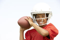 Junger Junge, der amerikanischen Fußball spielt Lizenzfreie Stockfotos