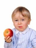 Junger Junge, der Apfel isst Stockbild
