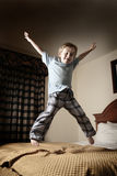 Junger Junge, der auf das Bett springt Lizenzfreies Stockbild