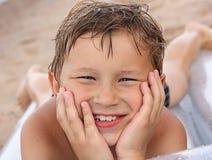 Junger Junge, der auf dem Strand liegt Stockfoto