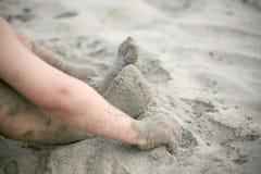 Junger Junge, der auf dem Strand spielt Lizenzfreie Stockfotos