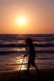 Junger Junge, der auf dem Strand während des Sonnenuntergangs spielt Stockfotos
