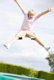 Junger Junge, der auf dem Trampolinelächeln springt Stockbilder