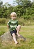 Junger Junge, der auf einem Felsen aufwirft Lizenzfreies Stockfoto