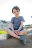 Junger Junge, der auf einem Felsen sitzt Lizenzfreie Stockbilder