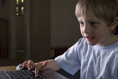 Junger Junge, der auf einem Laptop spielt Stockfotografie