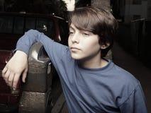Junger Junge, der auf einem Parkenmeßinstrument sich lehnt Stockbilder