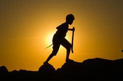 Junger Junge, der auf Felsen spielt Stockfotografie