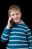 Junger Junge, der auf Handy spricht Stockbild