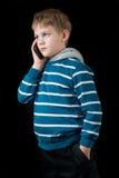 Junger Junge, der auf Handy spricht Lizenzfreie Stockfotografie