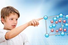 Junger Junge, der auf Moleküle 3D zeigt. Lizenzfreie Stockfotos