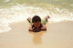 Junger Junge, der auf Sand legt Stockfotografie