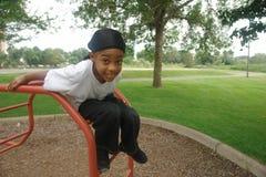 Junger Junge, der auf Spielplatz spielt Lizenzfreie Stockfotografie