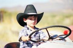 Junger Junge, der auf Traktor spielt Stockbild
