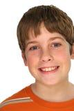 Junger Junge, der auf Weiß lächelt Stockbilder