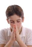 Junger Junge, der auf weißer vertikaler Mitte betet Stockfotografie