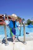 Junger Junge, der aus Swimmingpool auf Ferien heraus steigt Lizenzfreie Stockfotos