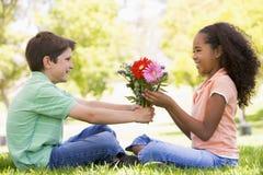 Junger Junge, der Blumen und das Lächeln des jungen Mädchens gibt Stockfoto