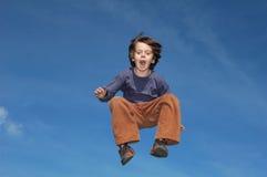 Junger Junge, der in den Himmel springt lizenzfreie stockfotografie
