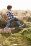Junger Junge, der in den Wellington-Matten spazierengeht Stockfotos