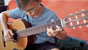 Junger Junge, der die Gitarre spielt stock video footage
