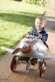 Junger Junge, der draußen beim Flugzeuglächeln spielt Stockbild