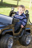 Junger Junge, der draußen beim Spielzeug-LKW-Lächeln spielt Stockfotos