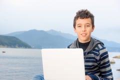 Junger Junge, der draußen Laptop verwendet. lizenzfreie stockbilder