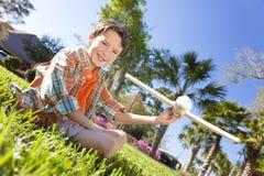 Junger Junge, der draußen mit vorbildlichem Flugzeug spielt Stockbild