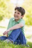 Junger Junge, der draußen sitzt Lizenzfreie Stockfotos