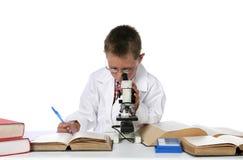Junger Junge, der durch Mikroskop schaut Stockfotografie