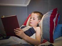 Junger Junge, der ein Buch liest Lizenzfreie Stockbilder
