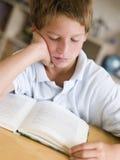 Junger Junge, der ein Buch in seinem Raum liest Stockbild