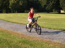 Junger Junge, der ein Fahrrad reitet Stockbild