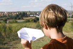 Junger Junge, der ein Papierflugzeug fliegt Lizenzfreies Stockfoto