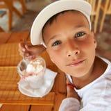 Junger Junge, der eine geschmackvolle Eiscreme im Freien isst Stockfotografie