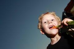 Junger Junge, der eine Karotte kaut lizenzfreie stockfotos