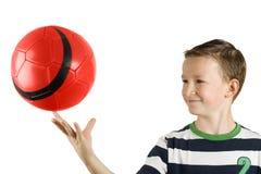 Junger Junge, der eine Kugel spielt Lizenzfreie Stockbilder